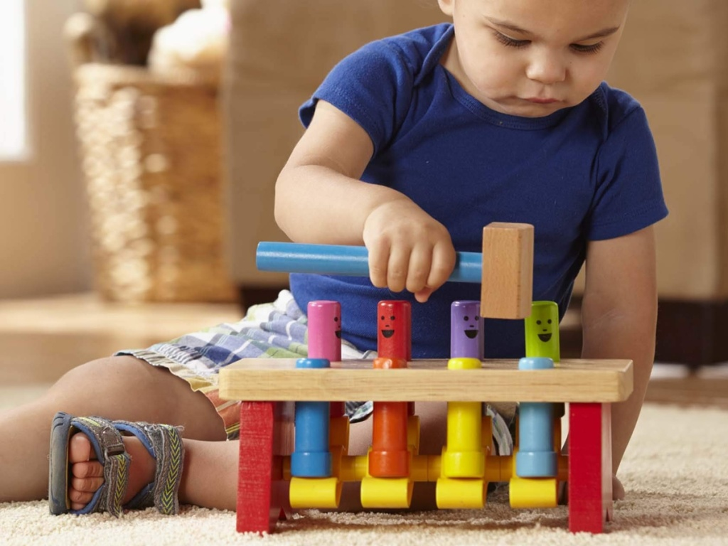 little boy sitting on the floor playing with a melissa and doug pounding bench