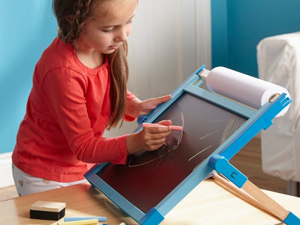 little girl drawing on a melissa and doug easel