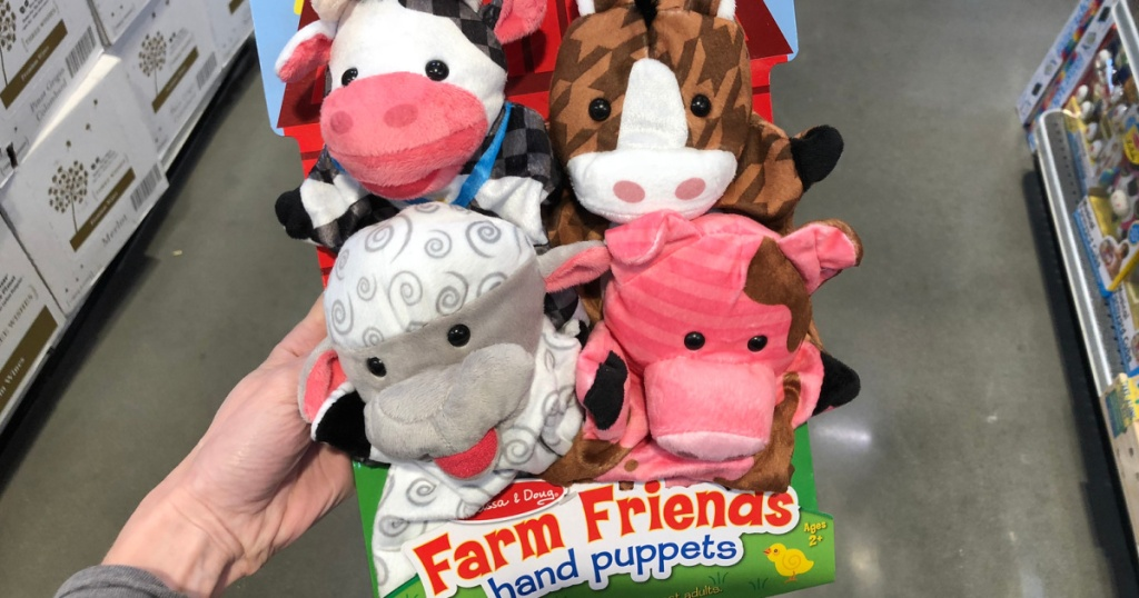 hand holding a melissa and doug farm friends hand puppets
