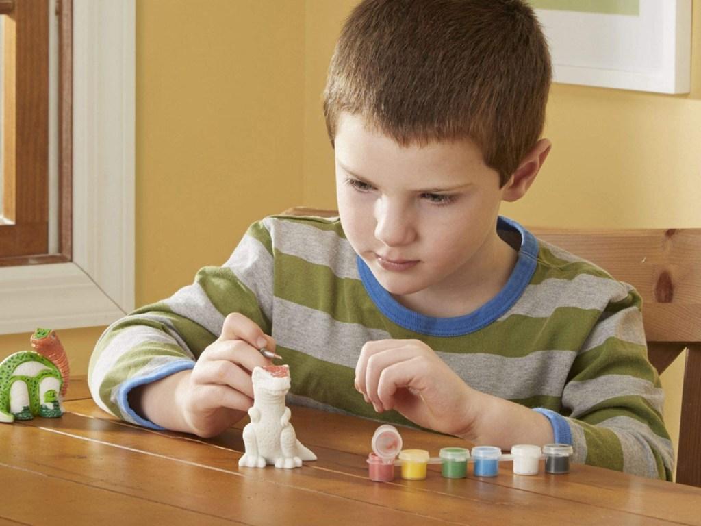 little boy painting a clay dinosaur