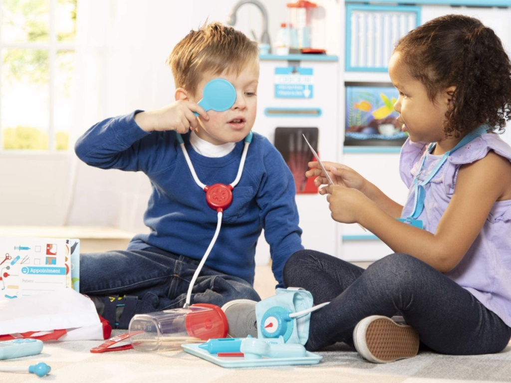 two children sitting on the floor playing with a melissa and doug doctor set