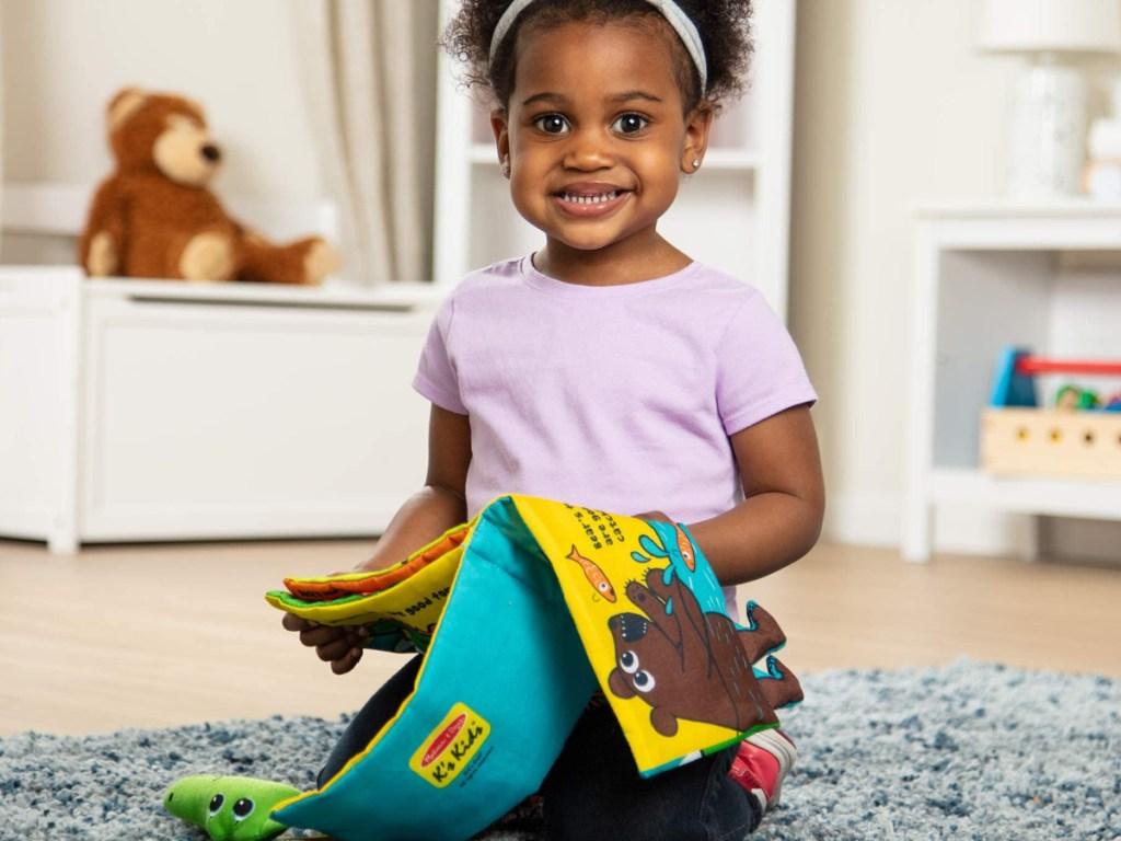 little girl kneeling on the floor holding a soft plush book