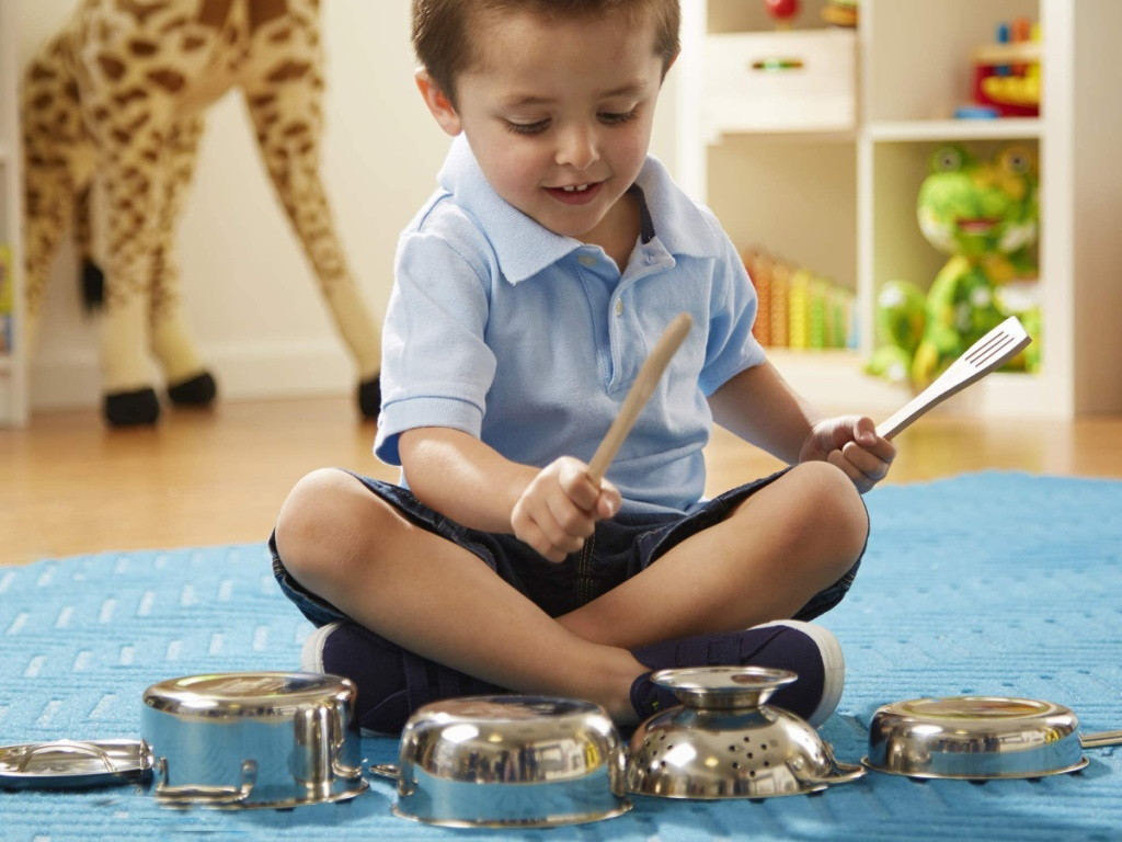little boy sitting on the floor playing with a melissa and doug pots and pans set