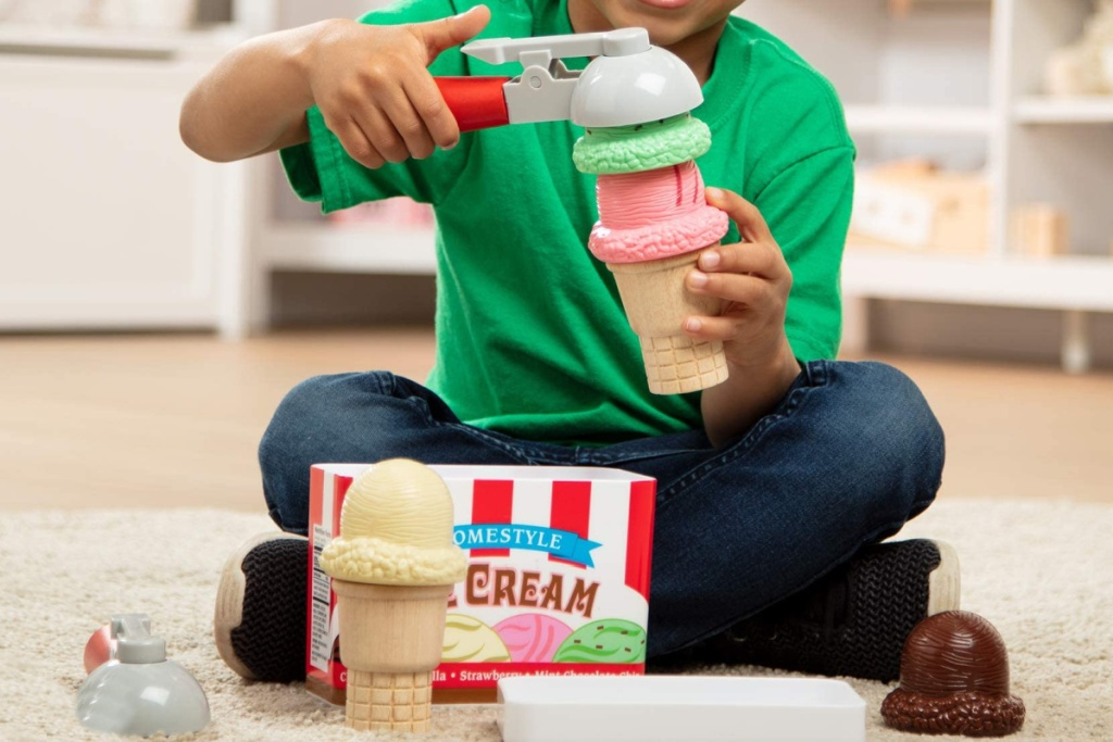 little boy playing with a melissa and doug wooden ice cream set
