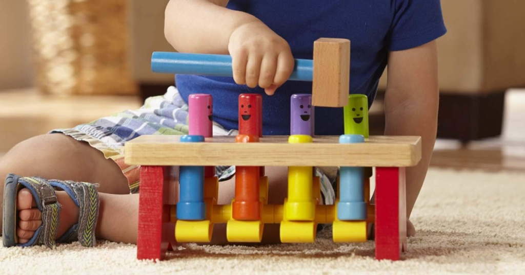 little boy playing with a melissa and doug wooden pounding bench