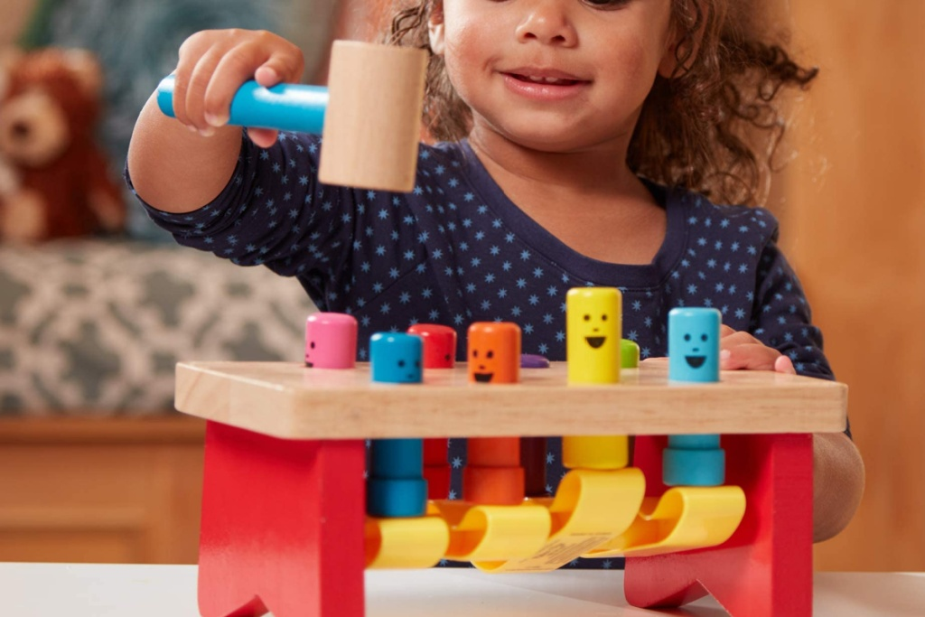 little girl playing with s melissa and doug wooden pounding bench