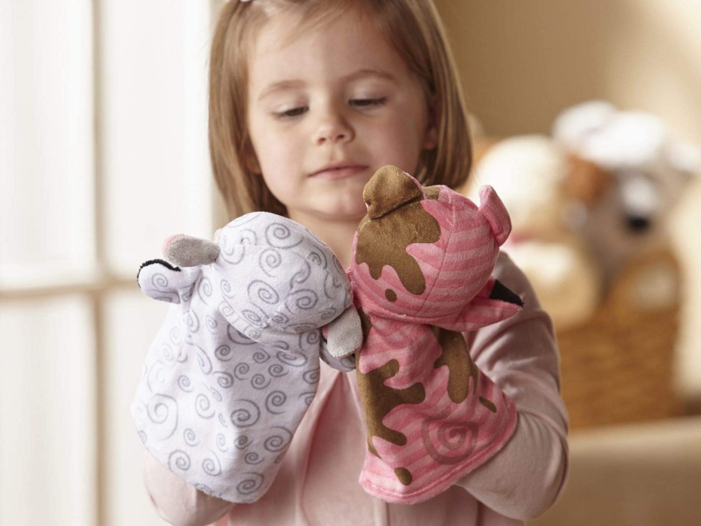 little girl playing with farm animals hand puppets
