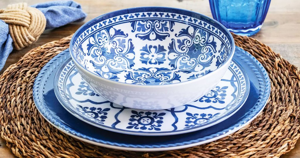 white and blue printed dinnerware set on a wicker placemat with blue napkin and cup in background