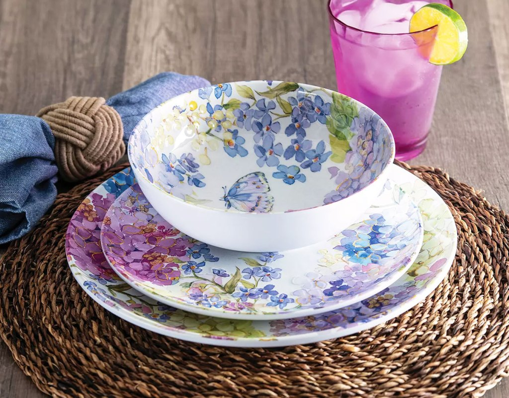 floral print dinnerware set on a wicket placemat with blue napkin and pink glass of water
