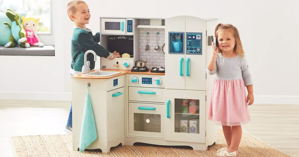 boy and girl playing with an L-shaped wooden kitchen set in a playroom