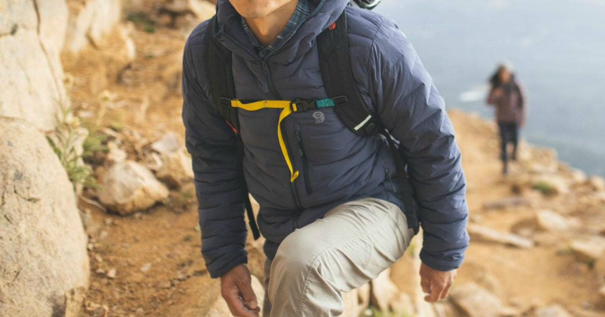 man wearing a climbing hoodie on a rocky surface