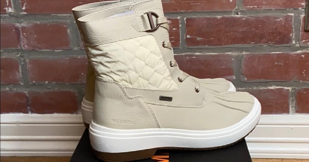sepatu bot musim dingin berwarna krem wanita di kotak sepatu