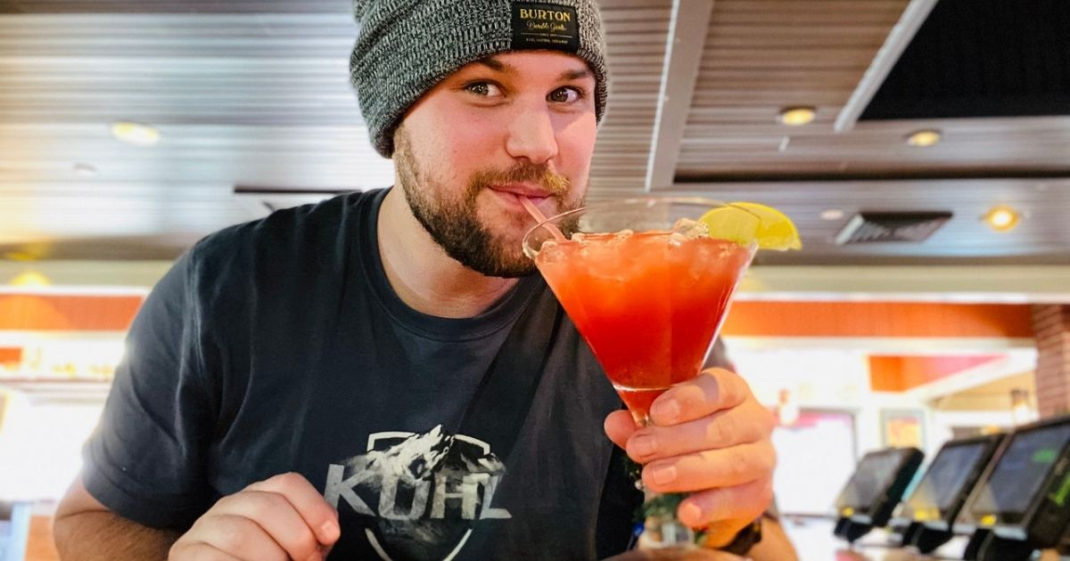Man drinking the Merry Berry margarita