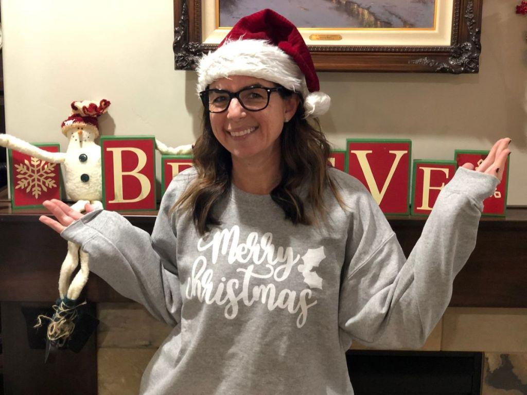 woman wearing a Santa hat and a Merry Christmas sweatshirt