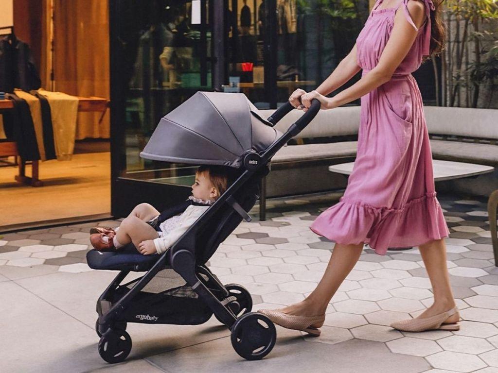 woman in pink dress pushing black stroller