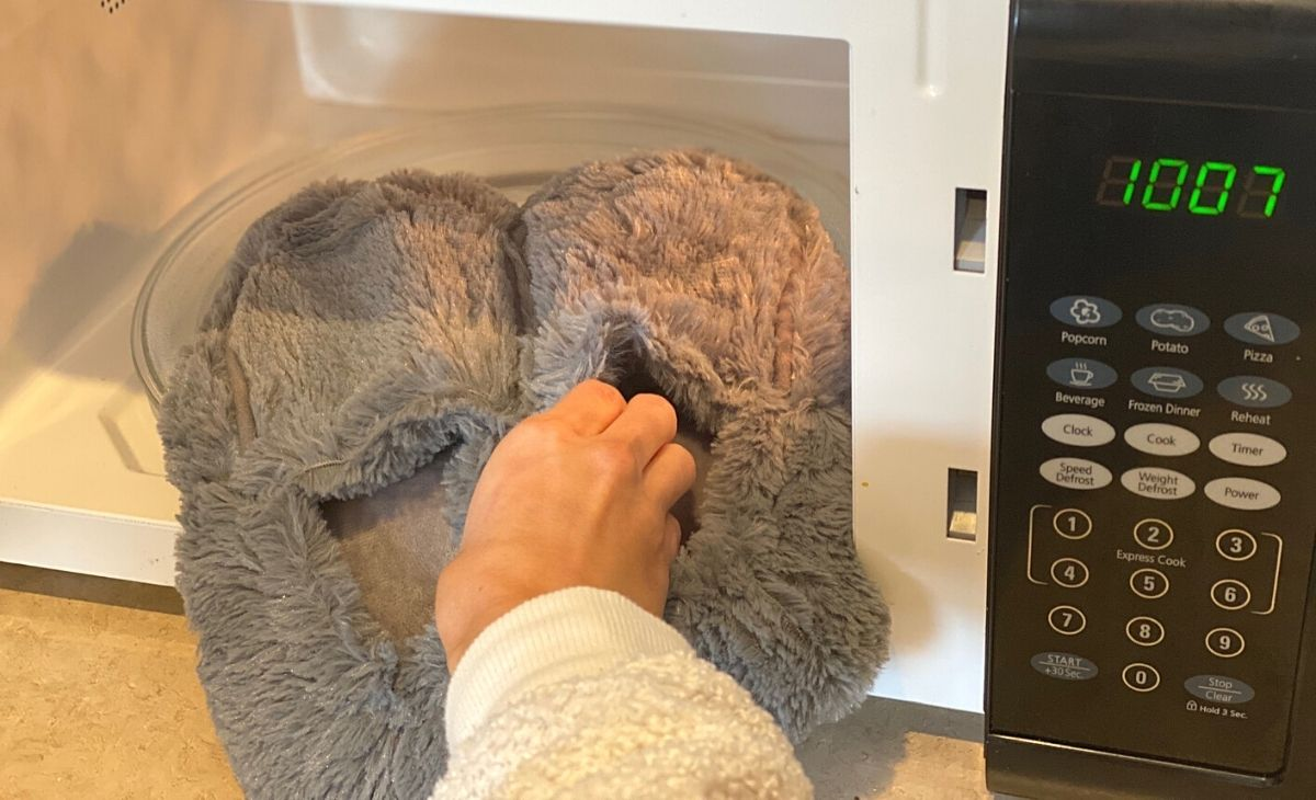A hand placing some slippers in the microwave
