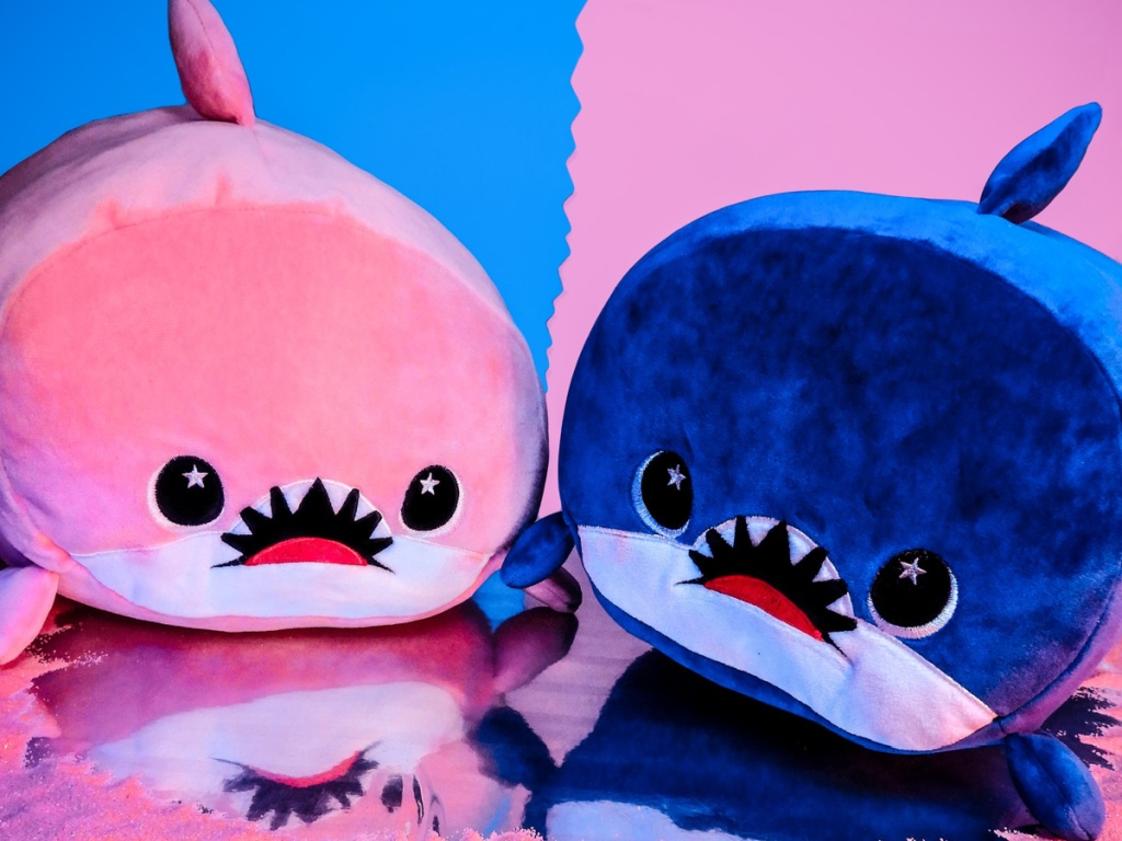 pink shark plush toy and blue shark plush toy