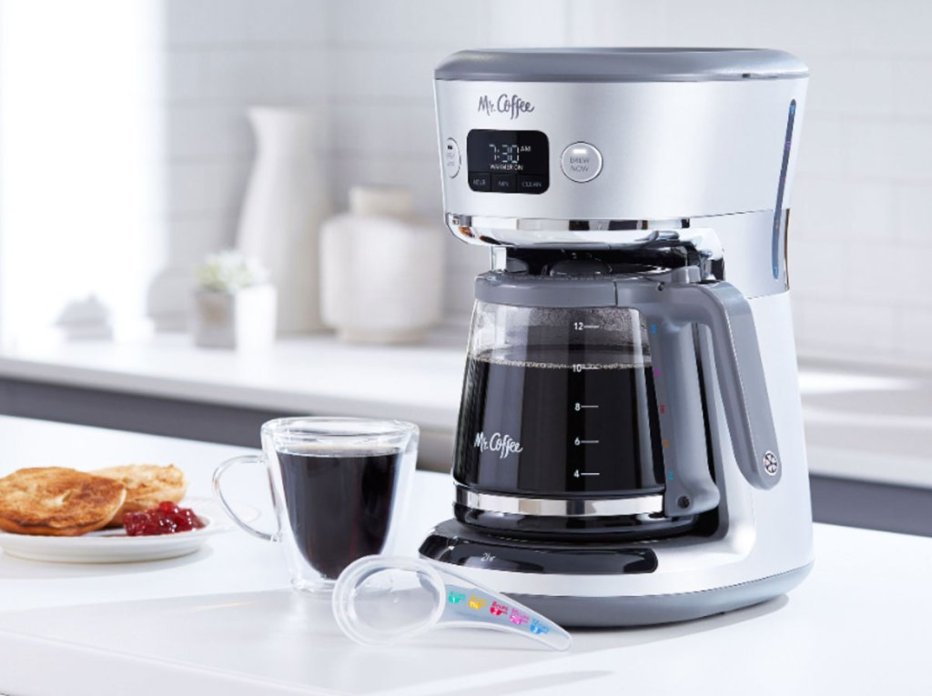 silver 12-cup mr coffee coffeemaker on kitchen counter with cup of coffee next to it