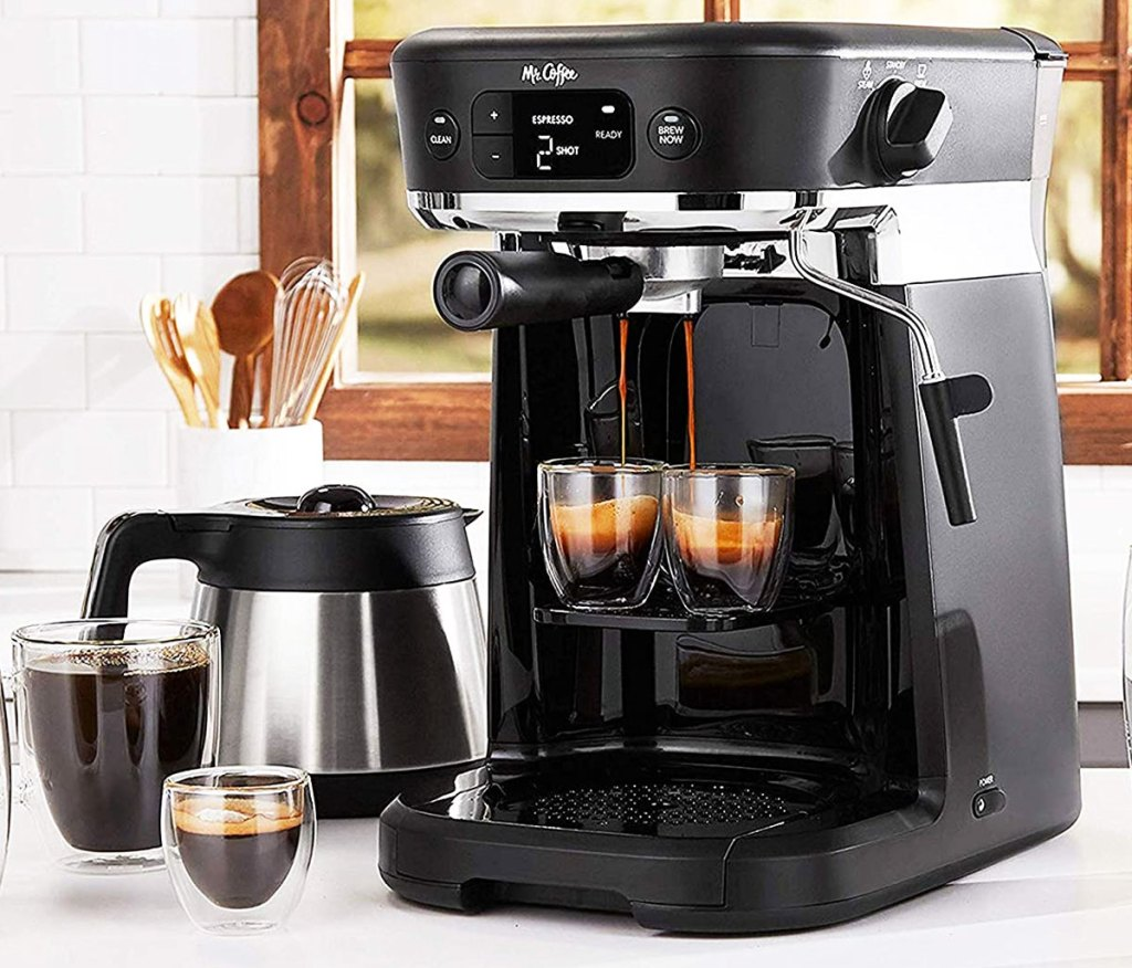black mr coffee coffee maker brewing two espresso shots with silver carafe and two cups of coffee next to it