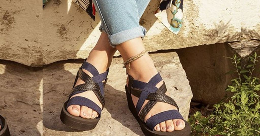 womans feet in blue and black sandals