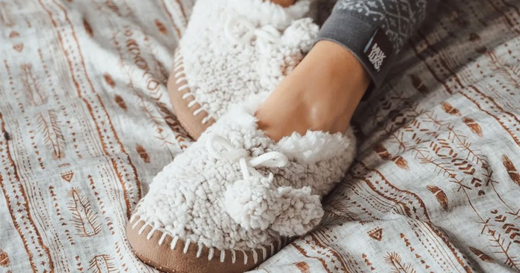 woman wearing a pair of sherpa ballerina slippers on a bed
