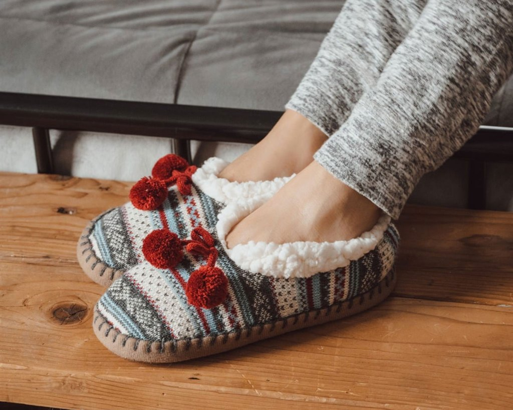 woman wearing pair of knit ballerina slippers with white sherpa interior