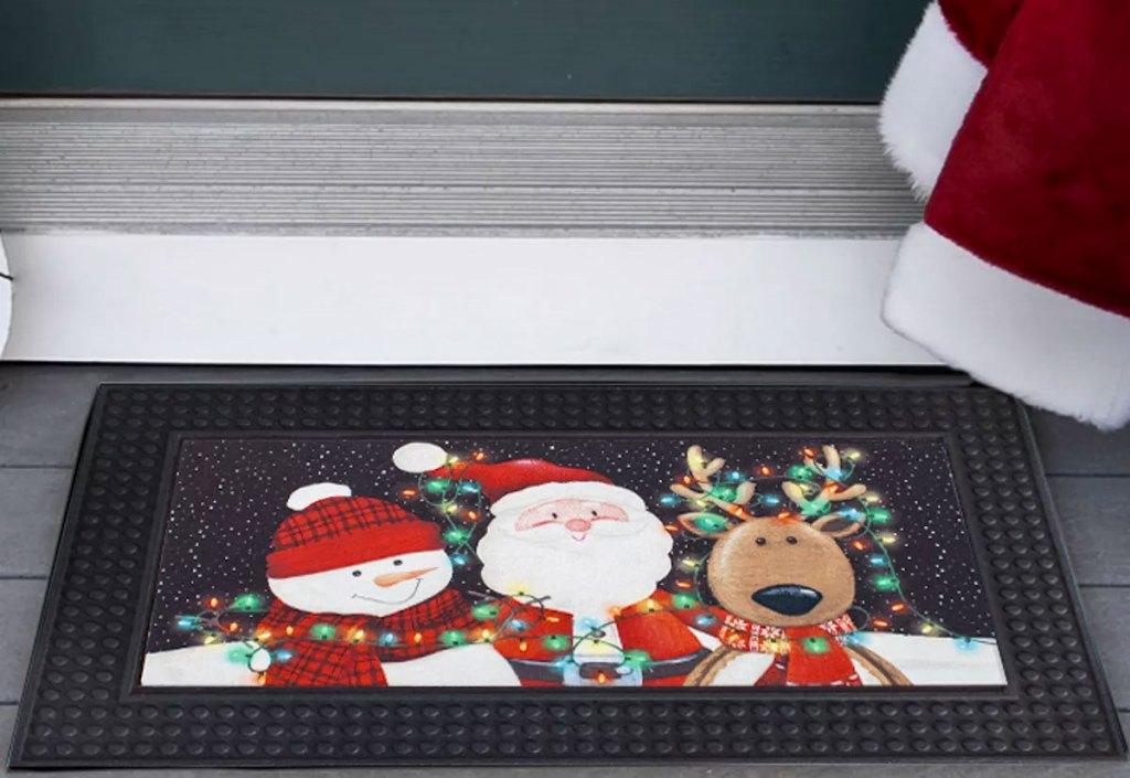 santa, snowman, and reindeer doormat at a front door
