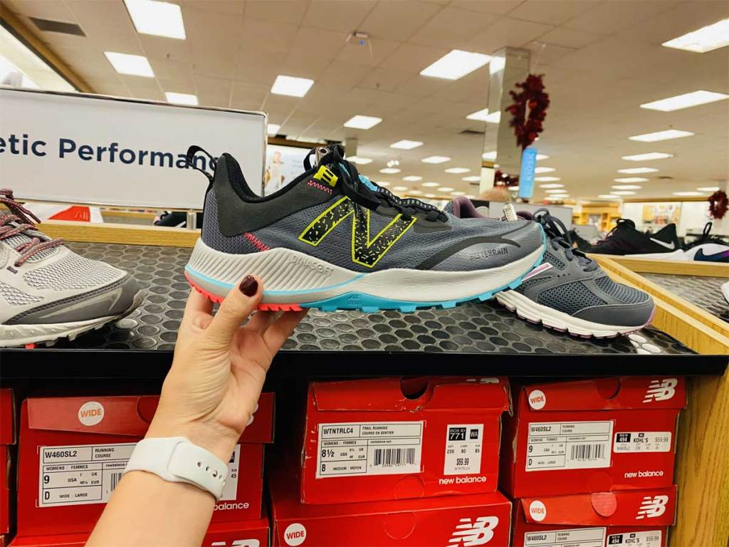 woman holding up a pair of running shoes in store