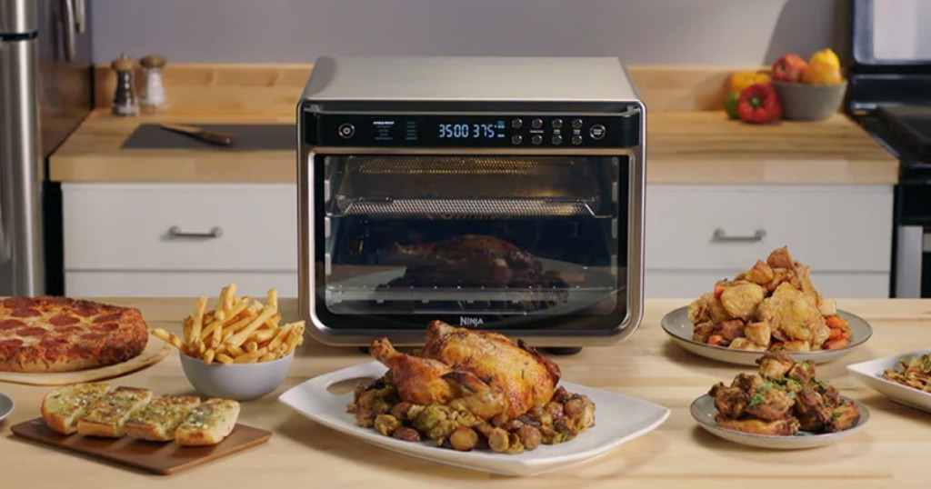 Ninja air fryer toaster oven on counter with fried foods