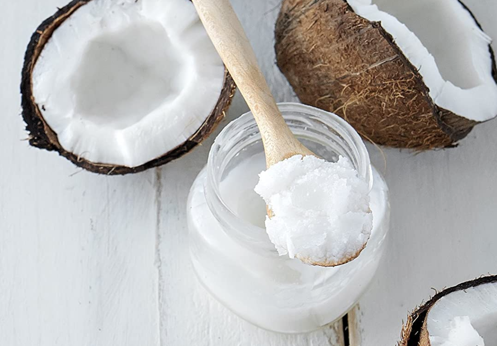 spoon of coconut oil with coconuts next to it