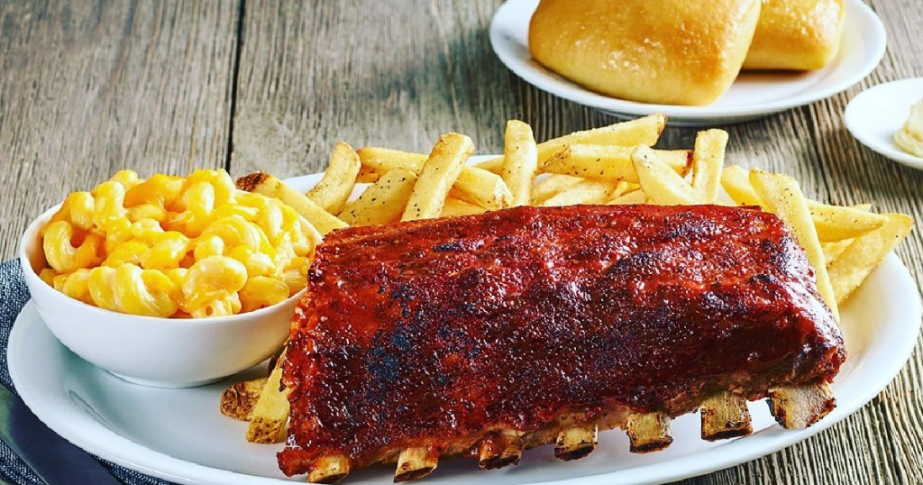 ribs, fries, and mac n cheese on plate and two rolls on small plate
