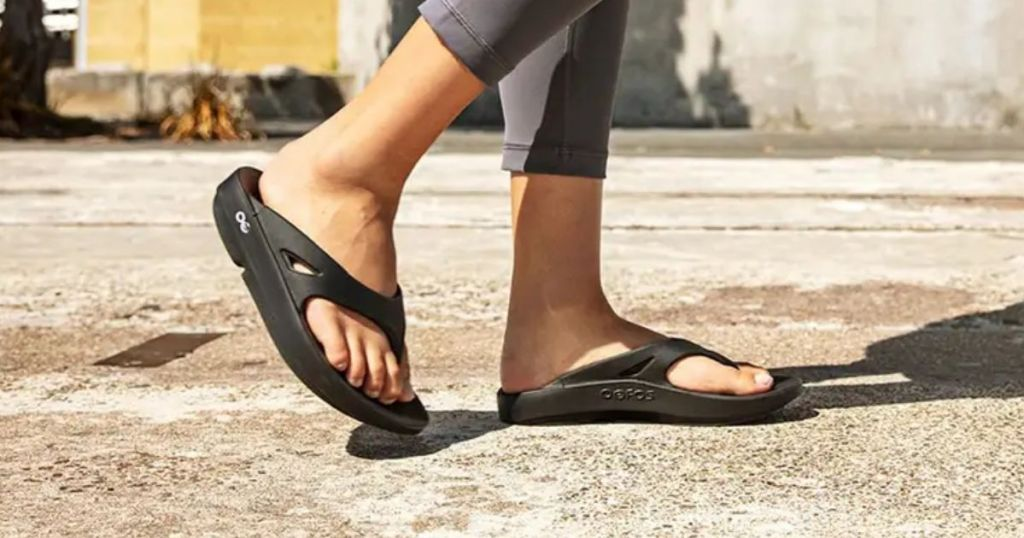 person walking in oofos sandals on concrete