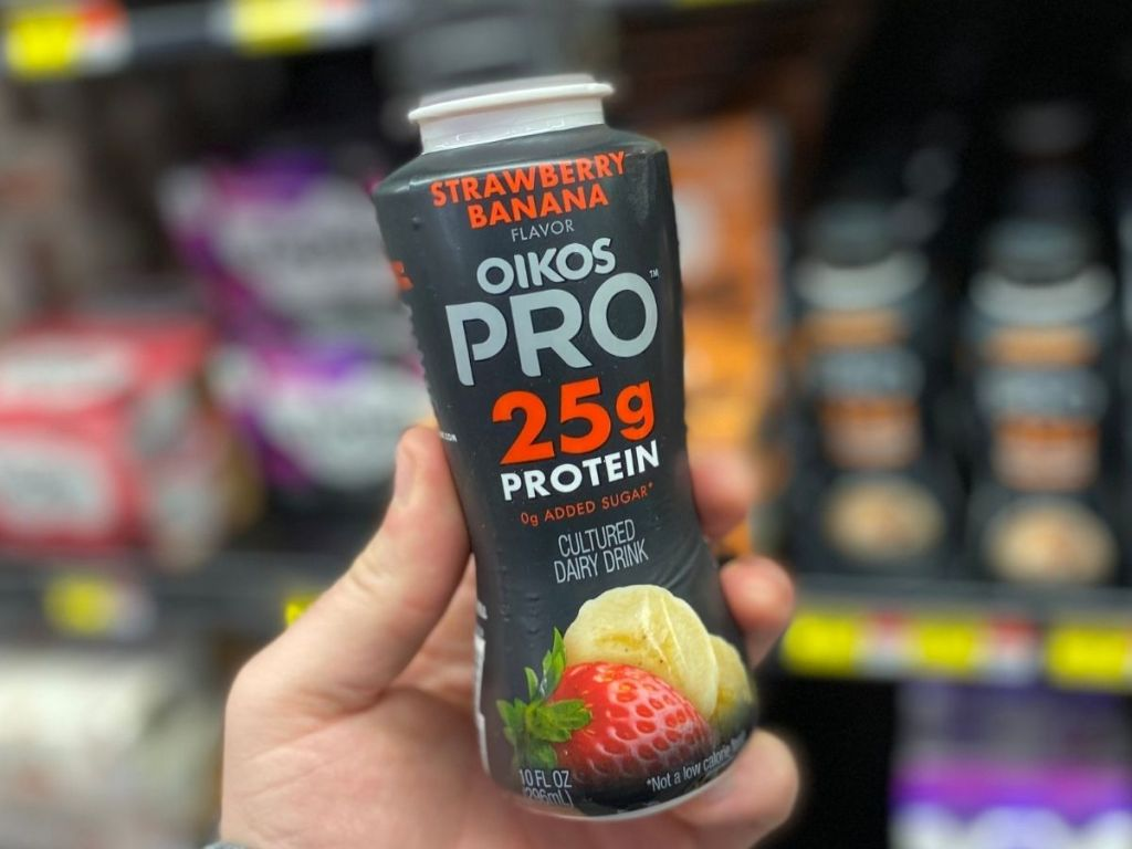Man holding strawberry banana Oikos Pro yogurt drink