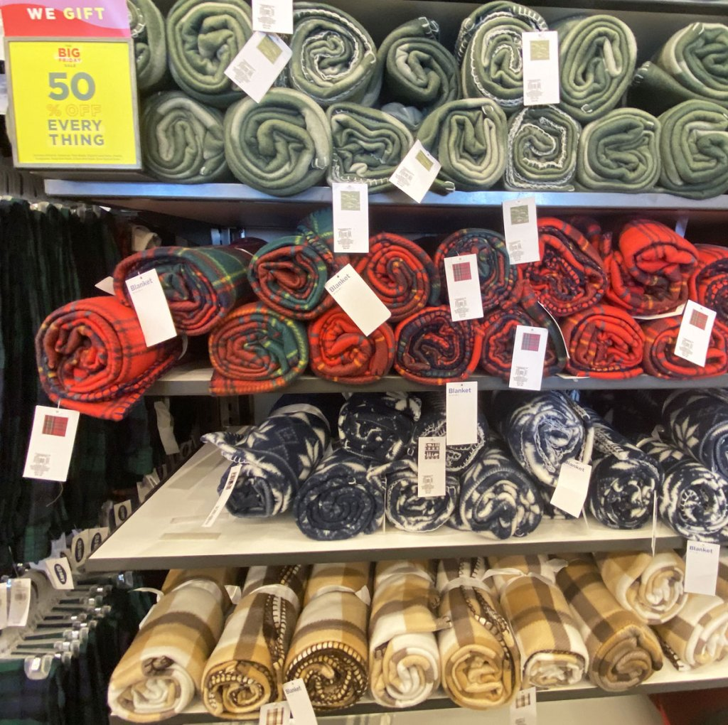 rolled up fleece blankets in a variety of prints on shelves at old navy