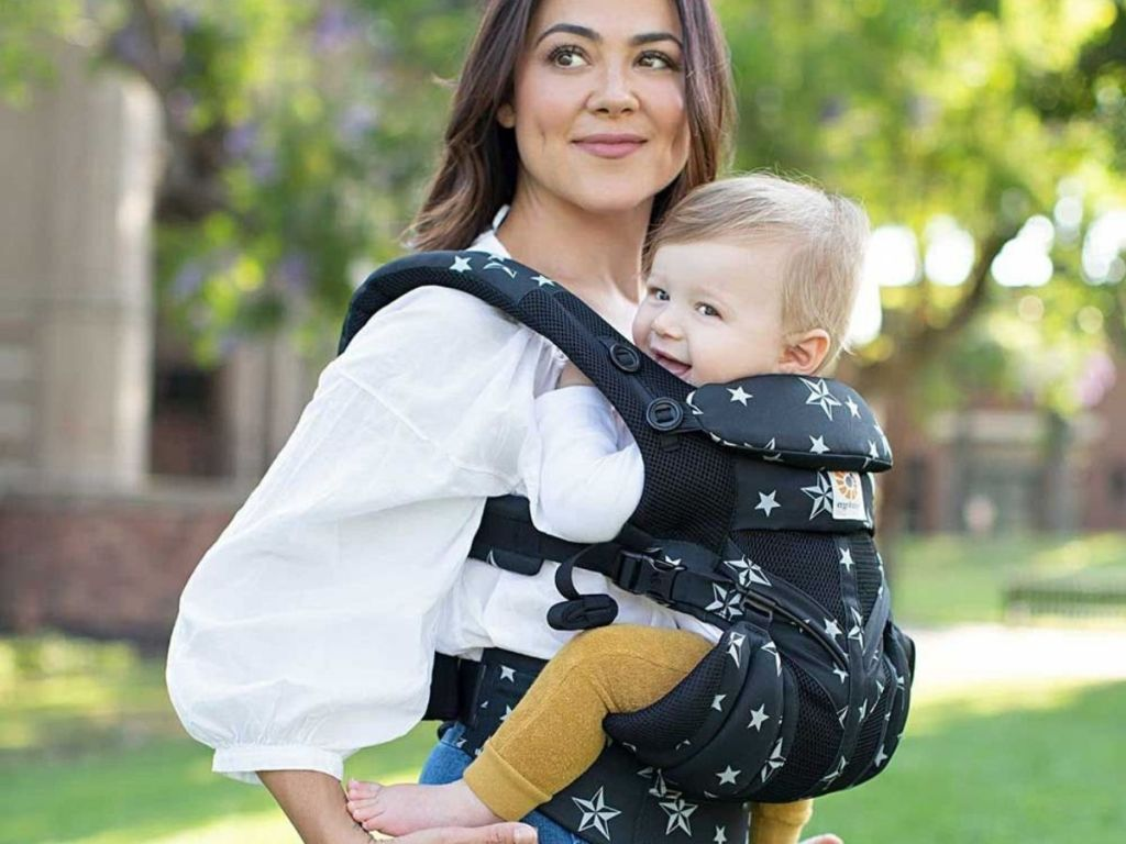 woman wearing blue and stars baby carrier