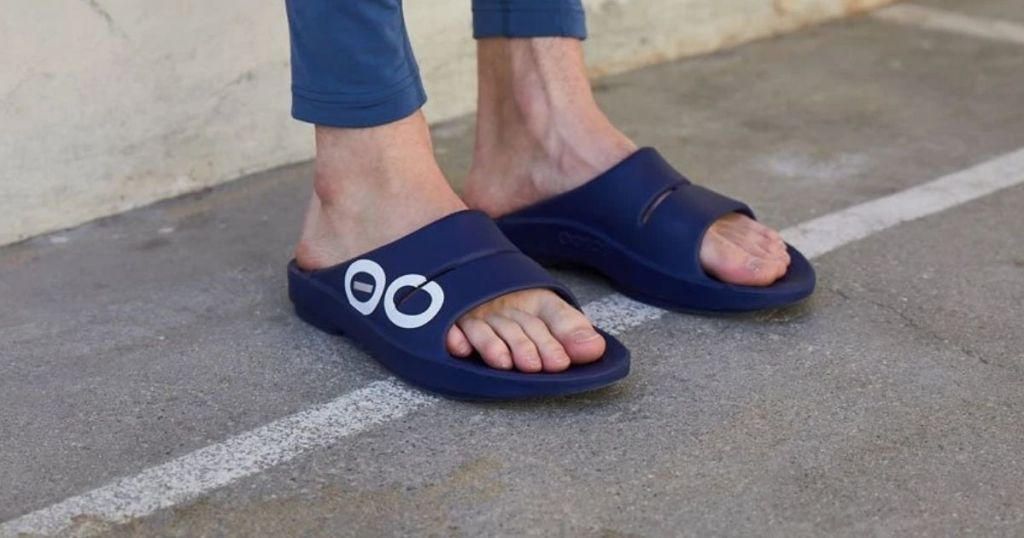 person wearing Oofos OOahh on cement