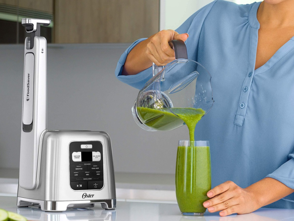 woman pouring a green smoothie into a glass next to an oster blender and foodsaver