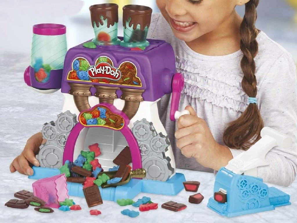little girl playing with play-doh candy playset