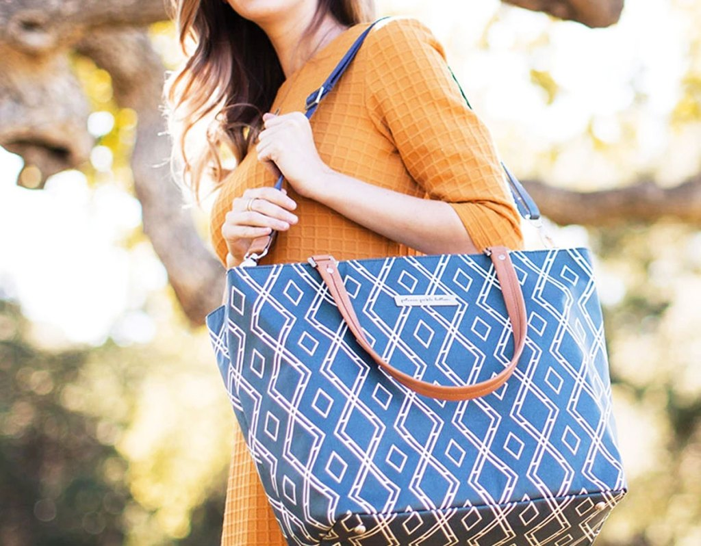 woman standing outside wearing orange dress holding a blue and white printed tote bag on her shoulder