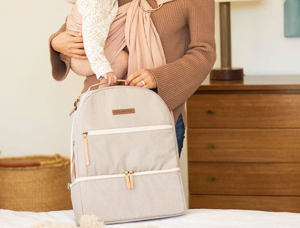 woman in brown sweater with baby in a sling with a grey baby bag backpack on bed in front of her