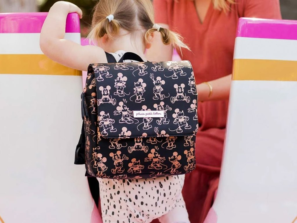 little girl with blonde hair in pigtails wearing a black backpack with rose gold mickey mouse print