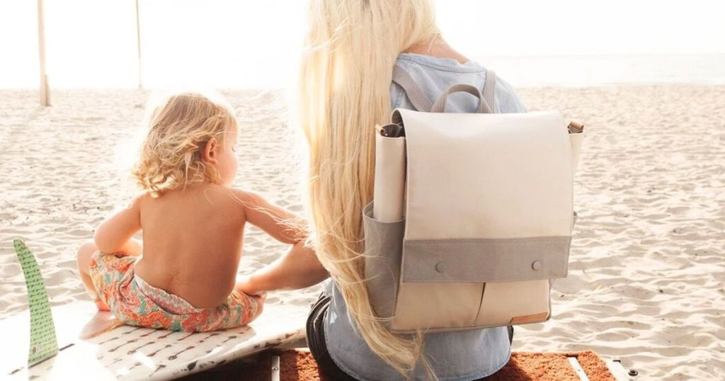 woman with blonde hair sitting next to a blonde boy on the beach with a white and grey backpack on her back