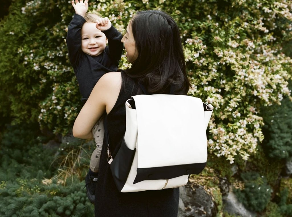 woman in black dress holding a boy in her arms with a white and black backpack on her back