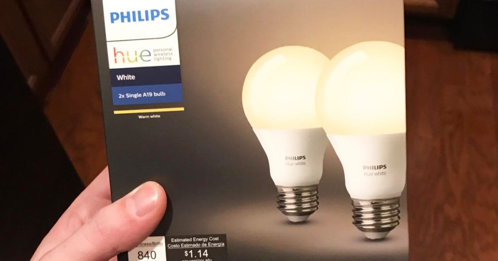 person holding up a box of two Phillips Hue white smart light bulbs