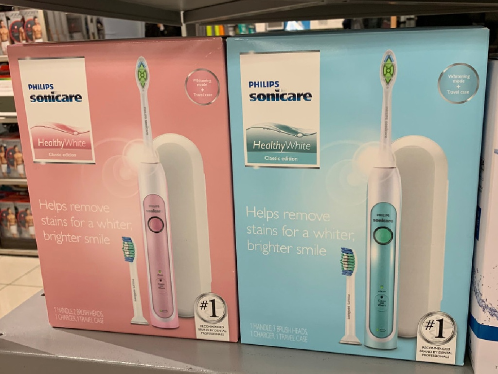 one blue electric toothbrush box and one pink electric toothbrush box on store shelf