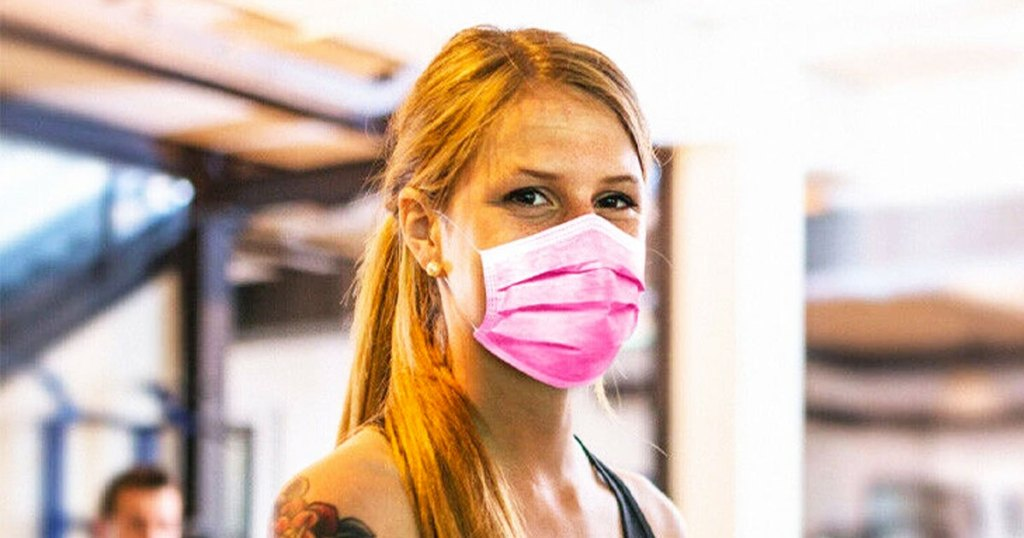woman with red hair wearing a pink disposable face mask