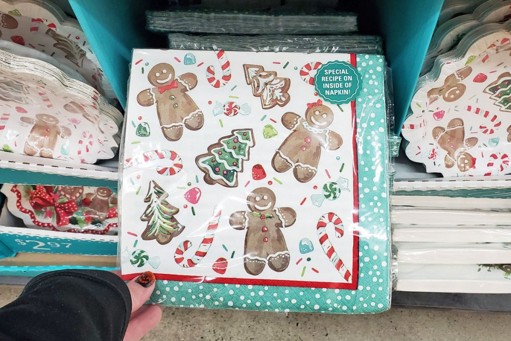 woman holding up a set of gingerbread man and christmas tree print paper napkins