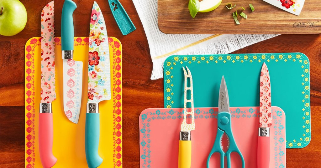 pink, yellow, and teal floral themed knife and cutting board set laid out in a kitchen