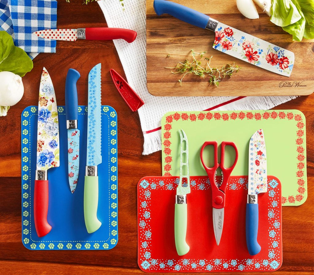 blue, red, and green floral themed knife and cutting board set laid out in a kitchen