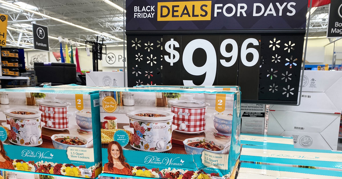 boxes of pioneer woman mini slow cooker 2-packs stacked at Walmart with $9.96 sale sign behind them